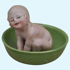 A charming Gebruder Heubach piano doll of baby bathing,