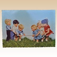 A wonderful Kathe Kruse postcard of a tug of war, German Child