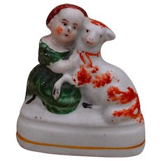 A miniature Staffordshire figure of a girl and a lamb, mid 19th Century