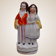 A miniature Staffordshire figure of a girl and a boy, 19th century