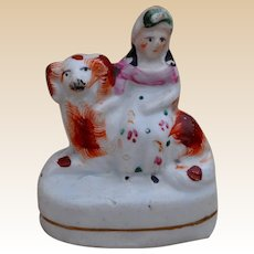 A miniature Staffordshire figure of a girl on her dog, mid 19th Century