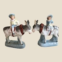 A beautiful pair of German bisque nodders of donkeys with children riders,