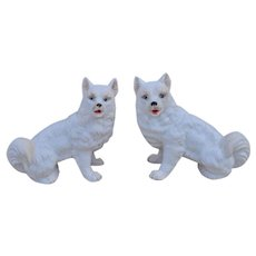 A pair of German bisque porcelain Spitz or Samoyed dogs, seated to left and right, circa 1900
