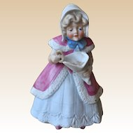 A German bisque figure of a girl with a cone of pretzels,