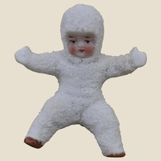 An antique large bisque Snow Baby seated,