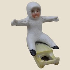 An antique large bisque Snow Baby on sleigh,