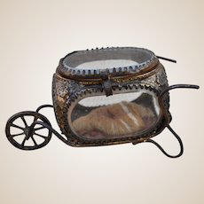 A charming French ormolu and bevelled glass trinket box in the form of a wheel barrow,