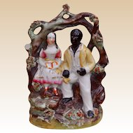A charming porcelaneous Staffordshire figure of Uncle Tom and Little Eva, 19th century