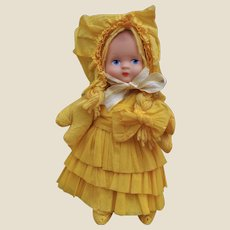 A celluloid faced doll with yellow crepe paper clothes, possibly off a Christmas cracker