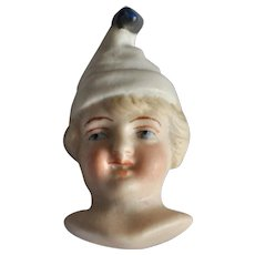 Rare bisque dolls face in clown's hat,