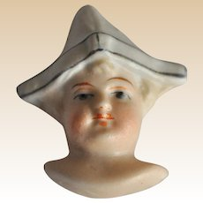 Rare bisque dolls face in folded paper party hat