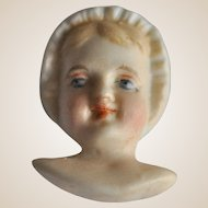 Rare bisque dolls face in bonnet,