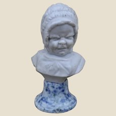 An unusual late 19th century doll size bisque bust of crying baby in bonnet,