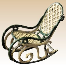 A lovely antique dolls' house cast metal 'bent wood'  rocking chair,