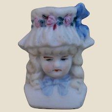 A German bisque shoulder-head with moulded hat,