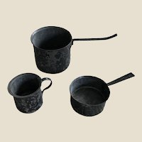 Three antique English tinplate dolls' house cooking vessels,