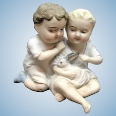 Dear little German Bisque Piano babies petting a rabbit