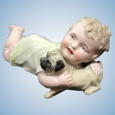 German Bisque Piano baby holding Pug Dog