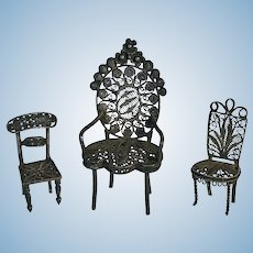 Three miniature white metal filigree chairs