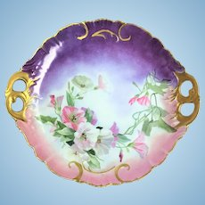 Limoges charger with honeysuckles against a pink and purple back ground