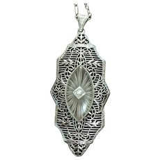 Art Deco 14 kt white carved rock crystal pendant set with a diamond.
