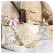 Set of old French lace pieces in a shabby fabric box for sewing or doll projects.