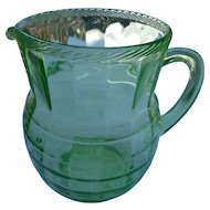 Large depression era green pitcher with applied handle graduated design