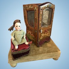 Antique doll palanquin from painted tin on the outside with great images of angels and flowers with an antique bisque doll.