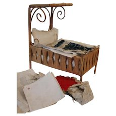 A Small Wicker Work Half Tester Dolls Bed, with lots of bedding