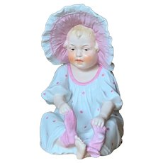 Unusual Heubach All Bisque Seated Figure with Pink and White Bonnet