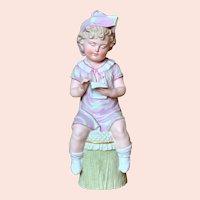 "12"" Gebruder Heubach figure of seated boy on stool."