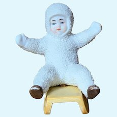 """3"""" tall German All Bisque seated """"Snow Baby"""" on sled."""