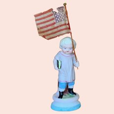 German All Bisque Boy figurine carrying American flag