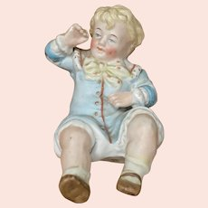 Heavy Bisque figurine of a boy that allows two seated positions.