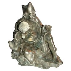 Chinese Silvered  Bronze Of Immortal, Seated And Holding A Fan and An Insect (Cicada)