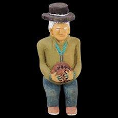 Johnson Antonio (Native American, Navajo, b. 1931 - ) Wood Carving, Seated Man Holding An Indian Shield
