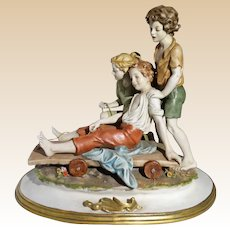 """Multi-Figural Bisque Porcelain """"Winter Fun"""" Three Children With A Sled"""