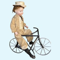 Antique French bisque doll toy on bicycle