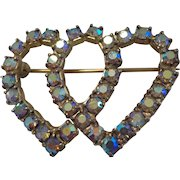 A Double Heart Pin set with Aurora Borealis colored Rhinestones