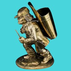 An antique silver drinking cup in the form of a traveller man statue