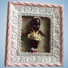 Tiny Brown Celluloid baby has its original skirt and bow and in a sweet little frame