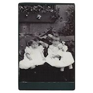 Cabinet Photograph Card Two Children (Girls) in Ruffled Dresses, Doll