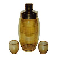 Striking gold glass shaker with geometric design and two matching glasses