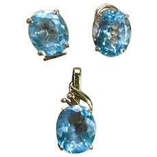 A classic blue topaz enhancer pendant with matching 14k oval cut blue topaz earrings.