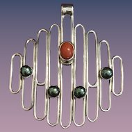 """A modernist style 950 silver signed """"Exel Tapia""""  silver pendant set with grey pearls and coral."""