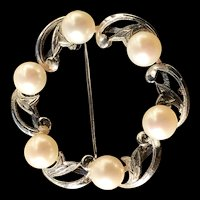 A lovely vintage silver mikimoto pearl circle pin.