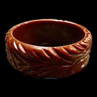 A chunky heavily carved vintage chocolate Bakelite bangle bracelet