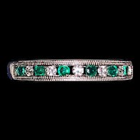 An estate 14k white gold diamond and emerald band ring.