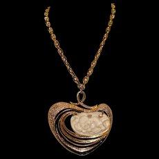 A chunky mid century Jomaz goldtone molded plastic pendant necklace.