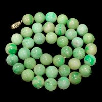 A fine quality 18k vibrant apple green jadeite beaded necklace.